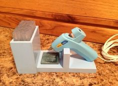 Glue gun stand with glue stick storage