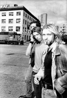 """Kurt Cobain and Nirvana were very much """"grunge"""". here they rock the layering including a flannel shirt. Long greasy hair was also part of the grunge style which is also shown here."""