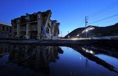 被災地の中でも最悪の割合となる人口の9%を超える人命が失われた宮城県女川町。横倒しになった4階建て鉄筋コンクリート製ビル。地盤沈下で満潮時はいまだに冠水。(毎日jp)