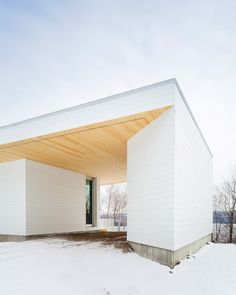 The two-storey house is clad in white-painted pine