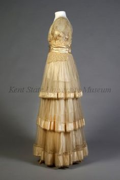 """1915 Wedding Gown, American. Cream satin, with tulle. Bodice portion has large satin W that starts at natural waistline and goes to Empire line. Top bodice portion is done in lace with tulle """"U"""" neckline. back forms a V with tulle and down front. WB connects at back right with hook and eye with loop cording. Short sleeves with satin band at cuff areas. Tulle drapery at shoulders. Ribbed internal 3"""" WB. Sidfe lace peplums. Three tiered tulle layered skirt with satin band around bottom."""