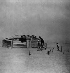 """Fleeing a dust storm"". Farmer Arthur Coble and sons walking in the face of a dust storm, Cimmaron County, Oklahoma. Arthur Rothstein, photographer, April, 1936."