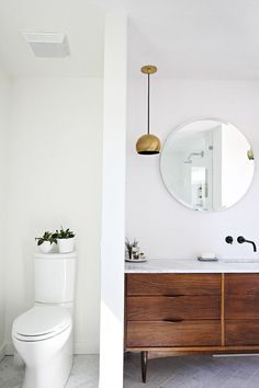 white, natural wood, and brass bathroom.
