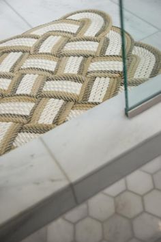 Marble hexagon shower tile paired with a complementary color variation of marble floors create a sandy, neutral backdrop to showcase an handwoven rug and set a spa-like experience underfoot.