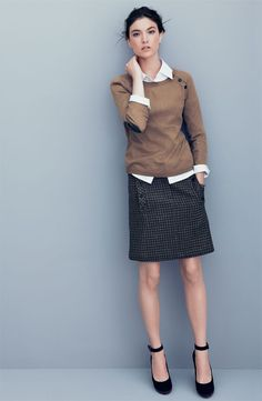 Untucked white blouse, brown sweater, gray textured knee length skirt