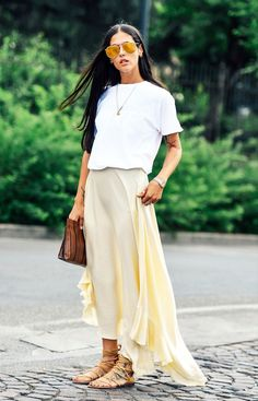 Street style look camiseta branca, saia midi e sandália amarrações.