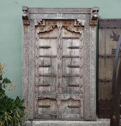 Original Rajasthani teak carved doors with surround.  Exquisite traditional carving patterns and details.  These beautiful doors are imported from India and show signs of age and sun bleached wood in excellent condition.