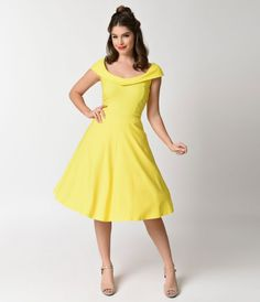 Dance into a little romance, darling. A vintage dress style that's beautifully crafted in an ethereal yellow. A cap sleeve princess seamed bodice boasts a plunging fold over v-neck in front and scoop back for divine flair. The lovely waist is tailored wit