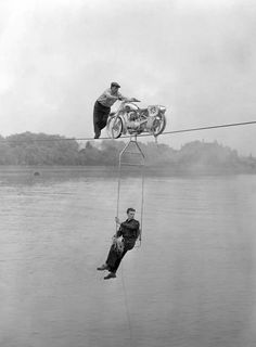 'Air Pirates' Alphonse and Charles Bugler pushes their stalled motorbike back across the Thames during a failed attempt to cross it by driving across a tightrope. They later succeeded with the stunt. 1954