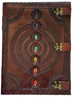 """7 Stone leather blank book w/ 3 latch    A massive tome with three latches to keep it closed and a line of 7 Chakra stones running down the front over the simple mandala centered on the cover. Embossing at the edge and on the rear cover may vary. Size may vary slightly. 180 blank, handmade, linen parchment paper pages. 13 1/2"""" x 18""""   Shop this product here: http://spreesy.com/Spiritspeaker/1   Shop all of our products at http://spreesy.com/Spiritspeaker      Pinterest selling powered by…"""