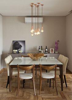 Sala de jantar elegante com vários pendentes iluminando a mesa