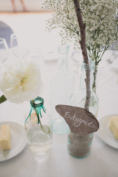 baby's breath with twig, and small bottle with one flower next to it. pretty touch to a table without getting spendy