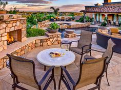 This Mediterranean stone patio offers several seating areas. There's one by the fireplace, one by the water feature and one with a view of the big sky above the home. A tile roof and classic turquoise columns on the home complete the look.