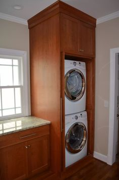 Custom Light Stained Wood Laundry Room, Double Stacked Washer and Dryer with Above Storage