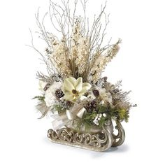 The striking Sleigh Ride Centerpiece is bursting with lifelike magnolia, hydrangea and delphinium blooms. Artistically arranged in a metallic sleigh, the champagne and cream blooms are accented by iced berries and branches, snow flocked pinecones and cedar greens.                    Hand-arranged polyester silk blooms and leaves                         Glitter mesh and velvet ribbon decoration                         Centerpiece rests in a resin sleigh planter with metallic finish      ...
