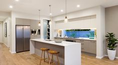 L shape window splashback and breakfast bar and beam above to divide kitchen from next room