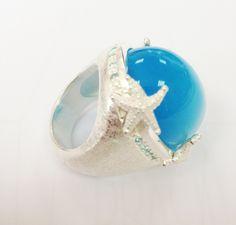 Neptuns Garden gr. Ring mit synth. blauem Tigerauge Cabuchon aus Silber mit Topas Pavee.Weite 54.