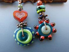 Asymmetrical Lampwork Bead Earrings in Greens and by tamajesyroar