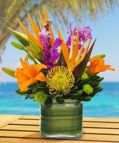 The orange lilies, mokara orchids, green kermit button mums and birds of paradise put out warm tropical vibes as this arrangement will brighten up any room. Tropical Centerpieces, Tropical Flower Arrangements, Wedding Flower Arrangements, Wedding Flowers, Exotic Flowers, Tropical Flowers, Summer Flowers, Beautiful Flowers, Cactus Flower