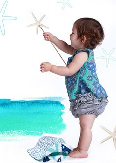 """For spring-summer 2014, Dipali Patwa at Masala Baby channels the bright sun and cool ocean tones of the Cape Cod beach. Here, a baby waves a sea-inspired """"wand"""" wearing a tile-patterned tunic and ruffle-tiered bloomers. A big reversible sunhat provides shade. www.masalababy.com (designer preview)"""