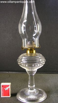 "As yet, we haven't been able to identify the maker of this little ribbed glass antique oil lamp. It has a simple design with horizontal ribs around the font, a plain stem and radiating ribs or icicles on the base. The same lamp is shown on page 89 fig.(g) of Catherine Thuro's first book ""Oil Lamps – The Kerosene Era in North America"". She dates this and similar ribbed glass lamps to the 1860s."