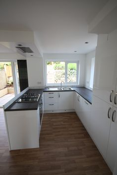 gloss white kitchen peninsular units with flush ceiling extractor in drop box and vertical radiator