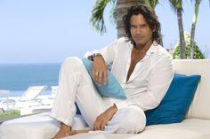 esta imagen nos muestra al actor Mario Cimarro en una playa muy tranquila y muy bonita rodeada de unas hermosas palmas