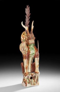 "Chinese Sancai-Glazed Figure of an Earth Spirit, Tang Dynasty (618-906 AD), of leonine form with antlers and a fierce expression, h. 34"", w. 8""."