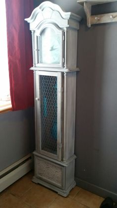 Grandfather clock farmhouse shabby chic w chicken wire front teal painted accents. Grey and white with dark and clear wax. Some silver rub and buff on edges to add appeal. Added porcelain knobs to doors. Paint able wall paper added to base front.
