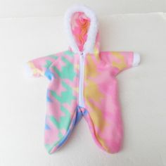 Keep your little sweetheart happy when you purchase this darling handmade light pink snowsuit. It has blue, green, yellow, and white print on