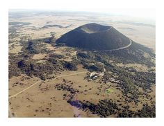 """Capulin volcano. After the cone was built, the first of three main lava flows issued from the """"boca"""" at the side of the crater. It was during this phase that at least two active lava lakes and a tube system formed and were used by erupting lava. Most of the tubes have collapsed over time. Several spatter cones have also been identified."""