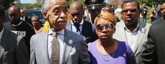 Lesley McSpadden, the mother of slain teenager Michael Brown, arrives for a press conference on the arm of civil rights leader Rev. Al Sharpton. (Scott Olsen/Getty Images)