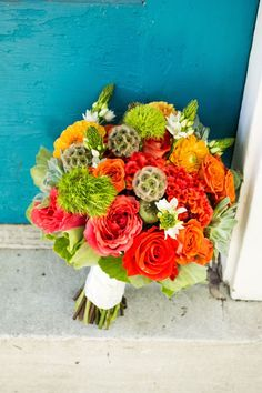 Textural summer bouquet in oranges and greens. Includes scabiosa pods, green trick, scented geranium, orange dahlias, orange roses, and succulents.