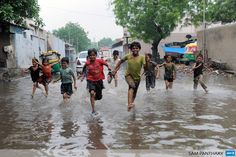INDIA, Ahmedabad: Indian children run across a flooded street in Ahmedabad on July 24, 2013. Heavy rains lashed many regions of Gujarat state and the Indian Meteorological Department (IMD) has warned of very heavy rains in Gujarat and surrounding regions in next 36 hours. AFP PHOTO / Sam PANTHAKY