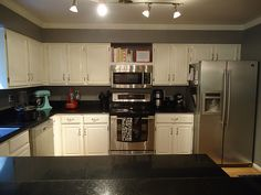 Gray walls, black granite, white cabinets, and pops of color appliances.