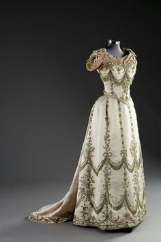 1888 evening dress by Worth has a scoop sweetheart neckline, partlet. Quarter-length tight sleeves, V-waist, small bustle,  and a close skirt.....Simply beautiful!