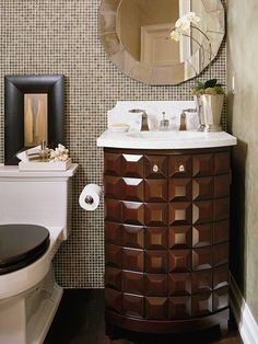 A powder room is a great place to showcase high style. It's a smart place to invest in luxurious products because this room is often frequented by guests, and its small footprint will keep your budget in order. Here, a wall of glass mosaic tile creates a dramatic backdrop for a glamorous retreat. A standout vanity echoes the rich tone, and a shapely toilet continues the geometric theme.