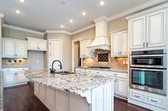 Open floor plan featuring antiqued white kitchen cabinets, Bianco Antico granite countertops, wood floors, travertine and metal backsplash, and a copper apron farmhouse sink