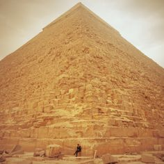 Sense of scale photo of a security guard sitting in front of the Pyramid in Giza, Cairo, Egypt.