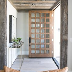 This floor-to-ceiling front door creates a welcoming entryway, with 32 charming glass window panes inset into the door's wooden frame!…