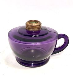 This listing is for a beautiful Amethyst purple antique pressed glass oil lamp with finger grip handle. It is 3.5 tall to top of brass ring and 3 across the base. It is in great working condition with no chips or damage. It does have seams visible from manufacturing. This lamp does not come with a chimney or burner but they are readily available at any good antique mall. Please note that the purple glass gets it color from prolonged exposure to the sun. In some cases that process is…