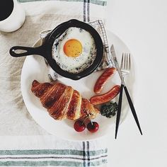 sausages, seasoned sunny side up, tomatoes, croissant, and coffee