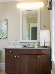 Accents such as bright contemporary artwork and bird sculptures add a bit of fun to this neutral bathroom.