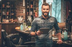 Keeping business on top with digital technologies Cheerful young bearded man looking at camera and h Stock Photo