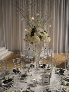 Tall white and silver wedding with candles and hydrangeas