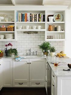 Bookshelf, tile, counters. White kitchen  subway tile open shelving