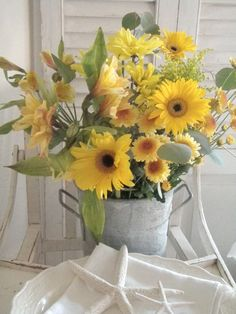 Gorgeous yellow flower arrangement in a vintage tin bucket makes for an uplifting centerpiece for your bumble bee themed wedding or summer event.