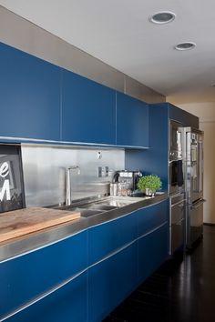 O azul domina a ambientação da cozinha que tem armários Brinna e eletrodomésticos em aço inox, da Viking. O piso de madeira ebanizada proporciona uniformidade ao espaço. O projeto de reforma do loft Itaim foi criado pelo escritório FGMF Arquitetos