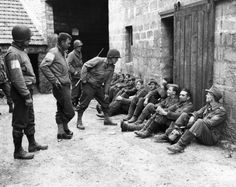 Three American soldiers, members of an airborne infantry outfit who were captured and held by the Germans near Orglandes, France on June 25, 1944, look at some of their former captors, now held by their comrades who captured the village and released the Americans. The soldiers are from left to right are front: Pfc, James C. Bishop, Dallas, Tex, Pvt. Joseph Burnett, Huntington, W.Va. and Pfc. (AP Photo) | Flashbak
