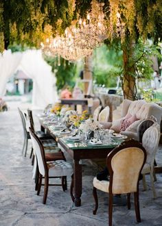 whimsical setting with mismatched seating and chandeliers in the trees --  shot by Michael + Anna Costa Photographers via Style Me Pretty
